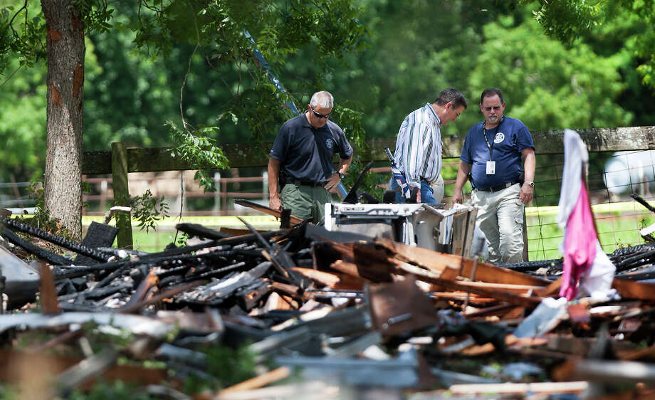 Investigators look through the debris after a home exploded, Tuesday, June 11, 2013, in Dobbin. Two people were transported to the hospital after the home exploded around 9 a.m. (Cody Duty / Houston Chronicle) Photo: Cody Duty, Houston Chronicle / © 2013 Houston Chronicle