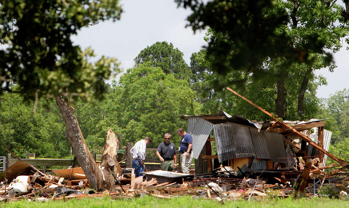 Investigators look through the debris after a home exploded, Tuesday, June 11, 2013, in Dobbin. Two people were transported to the hospital after the home exploded around 9 a.m. (Cody Duty / Houston Chronicle)