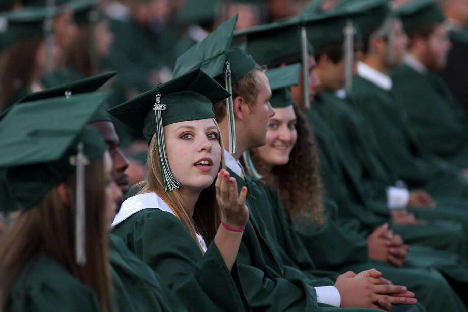 Kendra Dix blows a kiss to her parents and friends during the Clear Falls High School graduating ceremony at Veterans Memorial Stadium. Photo: Pin Lim, Freelance / Copyright Pin Lim.