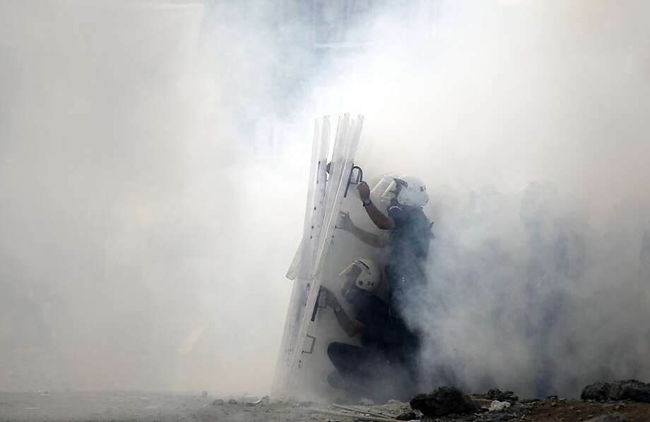 Policemen take cover amid a cloud of tear gas during clashes in Istanbul's Taksim Square. Photo: Kostas Tsironis, Associated Press
