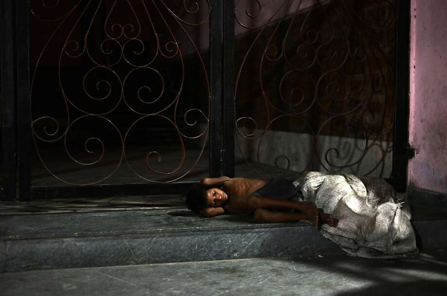 No life for a kid:Eight-year-old rag picker Barud sleeps on the doorstop of a building in Siliguri, India, after a day of collecting recyclables. June 12 is World Day Against Child Labor, which highlights the plight of children engaged in work that deprives them of adequate education, health, leisure and basic freedoms. Photo: Diptendu Dutta, AFP/Getty Images