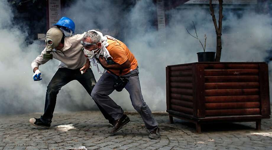 "Violence escalates in Istanbul:Ducking rubber bullets and tear gas canisters, two demonstrators try to escape from riot police in Taksim Square. Hundreds of police stormed the  square, the epicenter of nearly two weeks of unrest, in the early morning and brought bulldozers to clear makeshift barriers erected by demonstrators. Turkish Prime Minister Recep Tayyip Erdogan warned he would show ""no more tolerance"" for the unrelenting mass demonstrations against his Islamic-rooted government, not that he's shown any to begin with. Photo: Angelos Tzortzinis, AFP/Getty Images"
