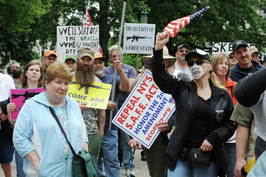 People hold signs during an anti-SAFE Act rally at the West Capitol Park on Tuesday, June 11, 2013 in Albany, N.Y.  (Lori Van Buren / Times Union) Photo: Lori Van Buren / 00022762A