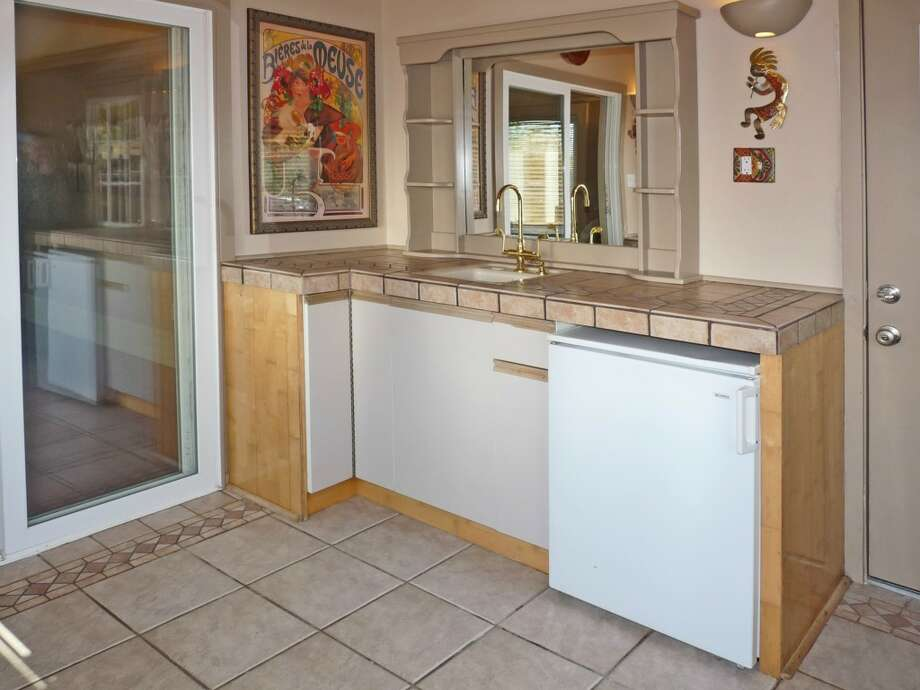 Wet bar of 5958 35th Ave. S.W. The 2,550-square-foot house, built in 1928, has four bedrooms, 2.25 bathrooms, beamed and vaulted ceilings, skylights, a sun room, a lower-level kitchen, a roof deck, a back deck and a covered patio on a 4,840-square-foot lot. It's listed for $467,000. Photo: Laura Timlick, Prudential Northwest Realty Associates
