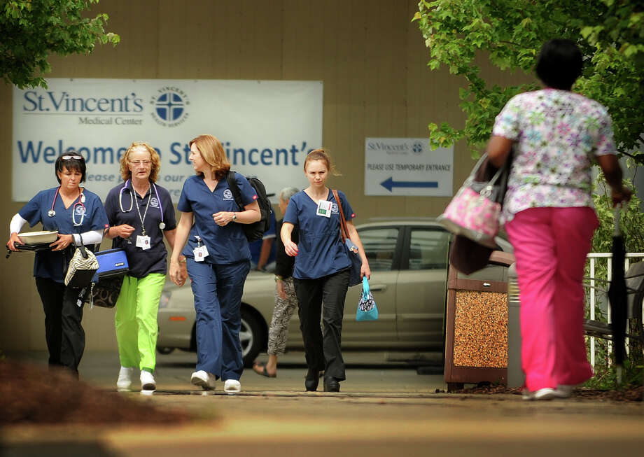 Employees cross paths during a shift change outside St. Vincent's Medical Center in Bridgeport, Conn. on Tuesday, June 11, 2013. The hospital announced layoffs of up to forty eight employees. Photo: Brian A. Pounds / Connecticut Post