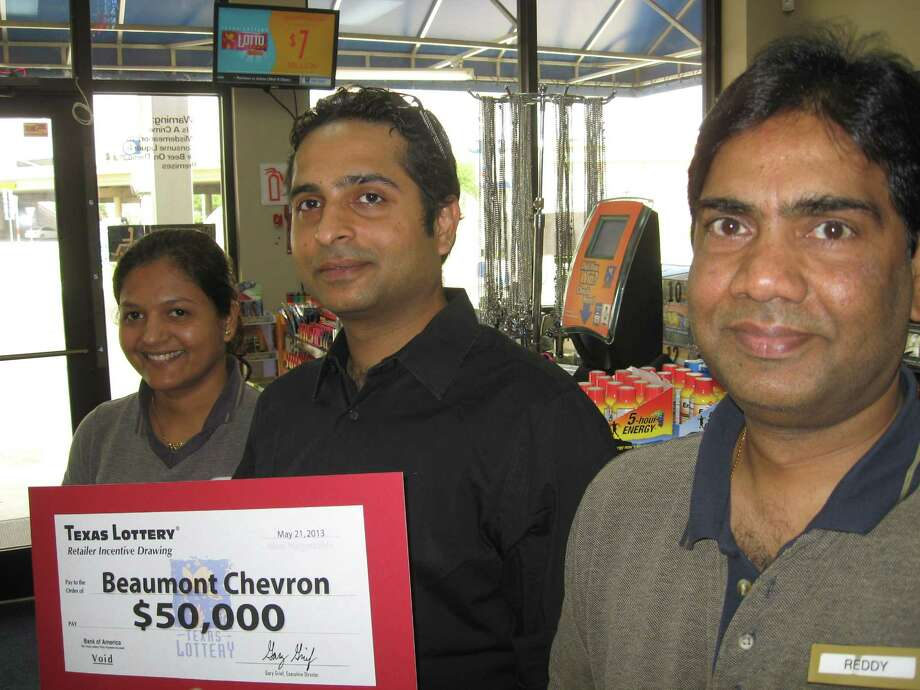 Sejal Patel, left; Kevin Akhani, store owner, center; and Reddy Seiry, right, celebrate Beaumont Chevron's winning of $50,000 from the Texas Lottery Commission for meeting and exceeding their store goal for sales of scratch-off tickets between Jan. 6 and April 6. The store is at College Street and Interstate 10. Only one other store in Texas won the top prize. Several other Southeast Texas stores won smaller cash prizes for meeting their goals. Dan Wallach/The Enterprise Photo: Dan Wallach