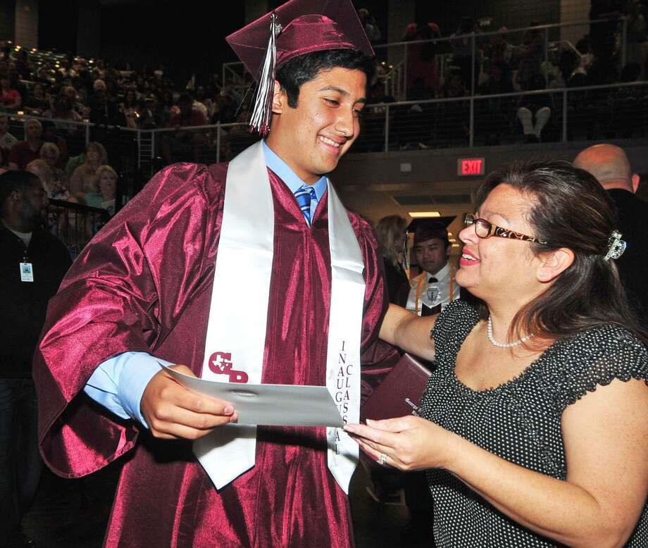 Joseph O. Chavarria is congratulated by Nikki Agner, George Ranch High School registrar clerk, after accepting his diploma during the school's first graduation on June 1.  Joseph O. Chavarria is congratulated by Nikki Agner, George Ranch High School registrar clerk, after accepting his diploma during the school's first graduation on June 1. Photo: Â Tony Bullard 2013, Freelance Photographer / © Tony Bullard & the Houston Chronicle