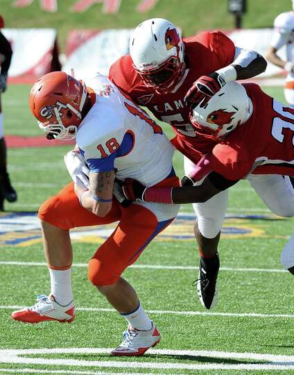 SHSU wide receiver Trey Diller is taken down by Lamar defensive players to gain another SHSU first d