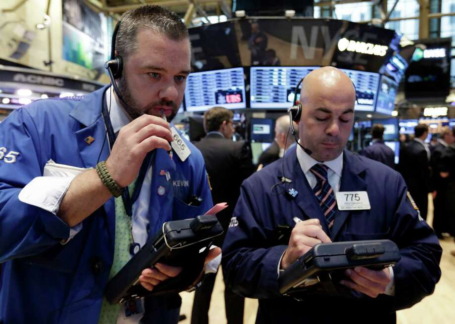 Traders Kevin Lodewick, left, and Fred DeMarco work on the floor of the New York Stock Exchange Tuesday, June 11, 2013. Stocks are falling in early trading on Wall Street, following global markets lower after the Bank of Japan declined to take further action to shore up that country's financial system. (AP Photo/Richard Drew) Photo: Richard Drew