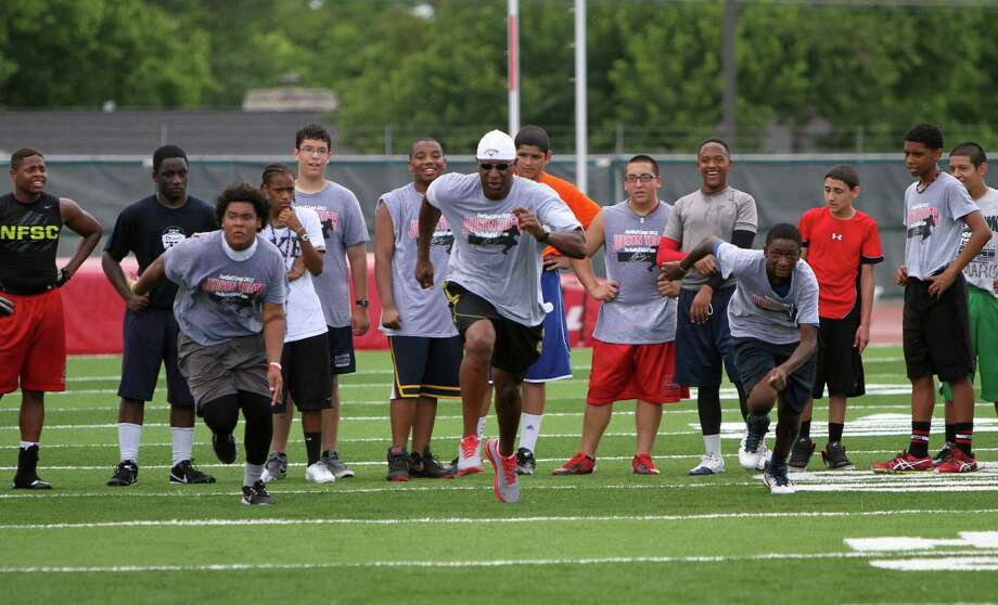 NFL Pro Football Hall of Famer Eric Dickerson (center) dashes downfield against two Judson Football Camp participants Sunday at D.W. Rutledge Stadium. Photo: Greg Bell / For The NE Herald