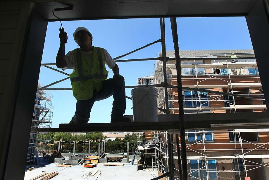 Philippe Perez applies paint to a window frame in a Redwood City apartment building under construction. Photo: Lance Iversen, The Chronicle