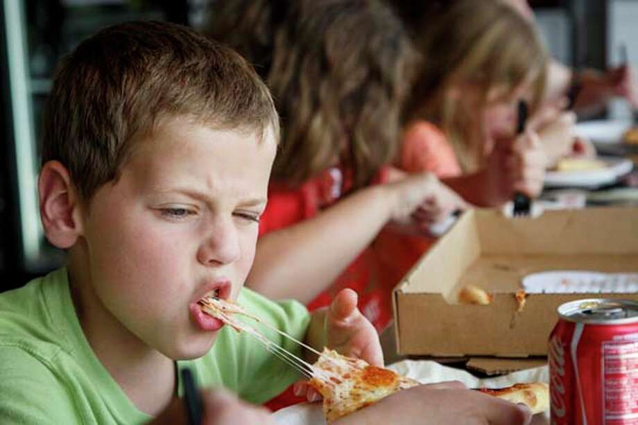 Joe Kendy IV, 7, bites into a piece of pizza at Pizza L'Vino. Photo: Michael Paulsen, Houston Chronicle / © 2013 Houston Chronicle