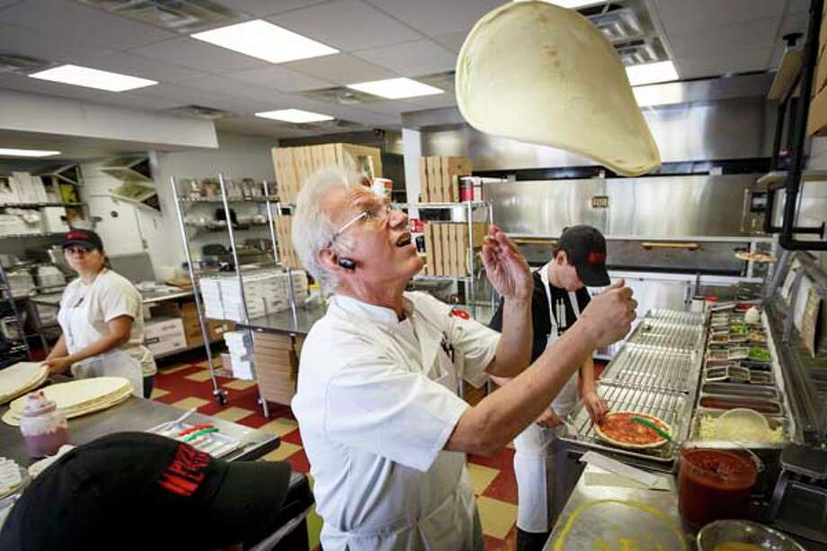 Ed Barnett flips pizza dough at Pizza L'Vino, a pizza restaurant that offers home delivery and takeout for pizza, beer and wine. Photo: Michael Paulsen, Houston Chronicle / © 2013 Houston Chronicle