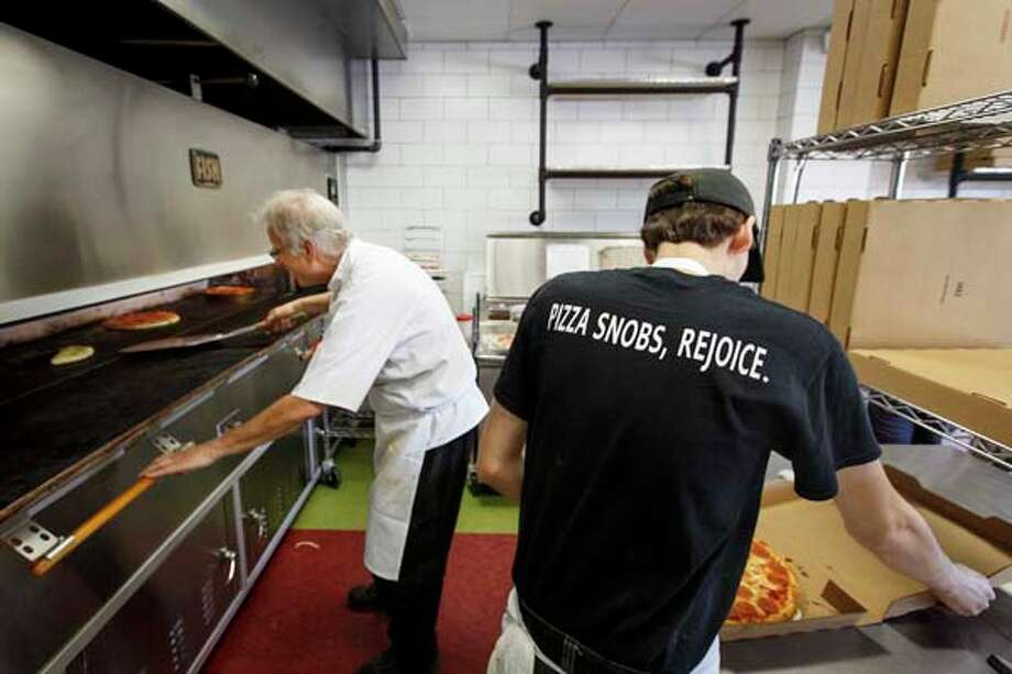 Ed Barnett, left, checks the oven while Aldous Politte boxes a pizza at Pizza L'Vino. Photo: Michael Paulsen, Houston Chronicle / © 2013 Houston Chronicle