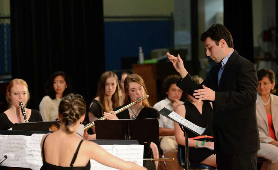 "Paul Frucht, right, conducts ""Dawn,"" a musical arrangement dedicated to former Assistant Principal and Honor Society Advisor Dawn Hochsprung, at the Junior Honor Society induction at Rogers Park Middle School in Danbury, Conn. on Tuesday, June 11, 2013.  Frucht, a student a the Juilliard School and former Danbury resident, wrote the song for Dawn, who was killed in the Dec. 14 shooting at Sandy Hook Elementary School. Photo: Tyler Sizemore / The News-Times"