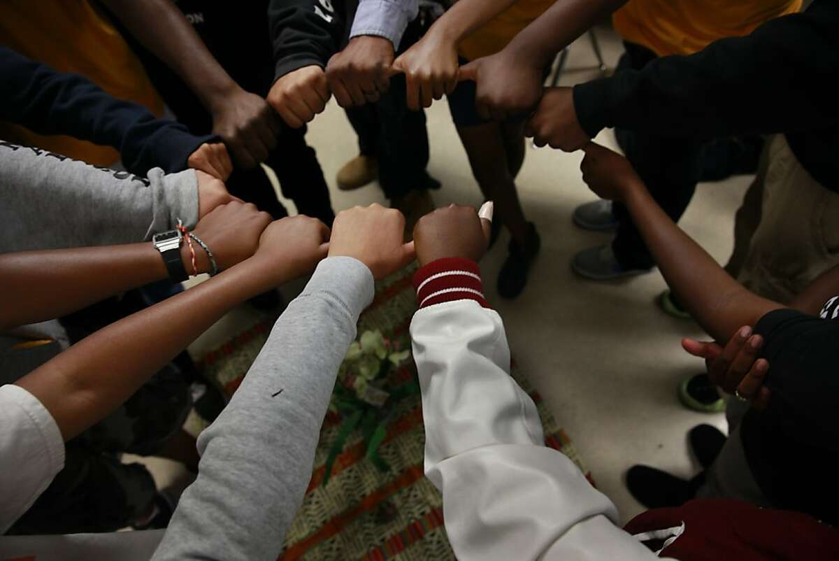 Kyle McClerkins, Restorative Justice coordinator, has students link thumbs to form a circle during a closing exercise on the last day that McClerkins met with the students for the school year at James Madison Middle school on Tuesday, June 11, 2013 in Oakland, Calif.