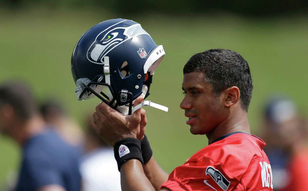 Seattle Seahawks quarterback Russell Wilson puts on his helmet during NFL football minicamp Tuesday, June 11, 2013, in Renton, Wash.