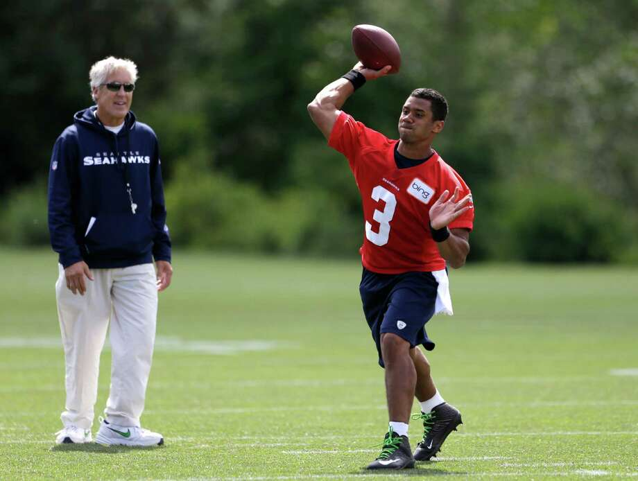 Seattle Seahawks head coach Pete Carroll, left, watches quarterback Russell Wilson toss around the ball following an NFL football minicamp Tuesday, June 11, 2013, in Renton, Wash. Photo: AP