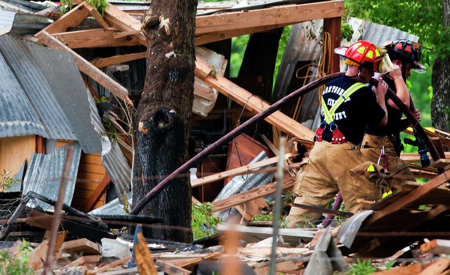 Firefighters carry a hose after putting out hotspots in the debris of a home that exploded, Tuesday, June 11, 2013, in Dobbin. Two people were transported to the hospital after the home exploded around 9 a.m. Photo: Cody Duty, Houston Chronicle / © 2013 Houston Chronicle