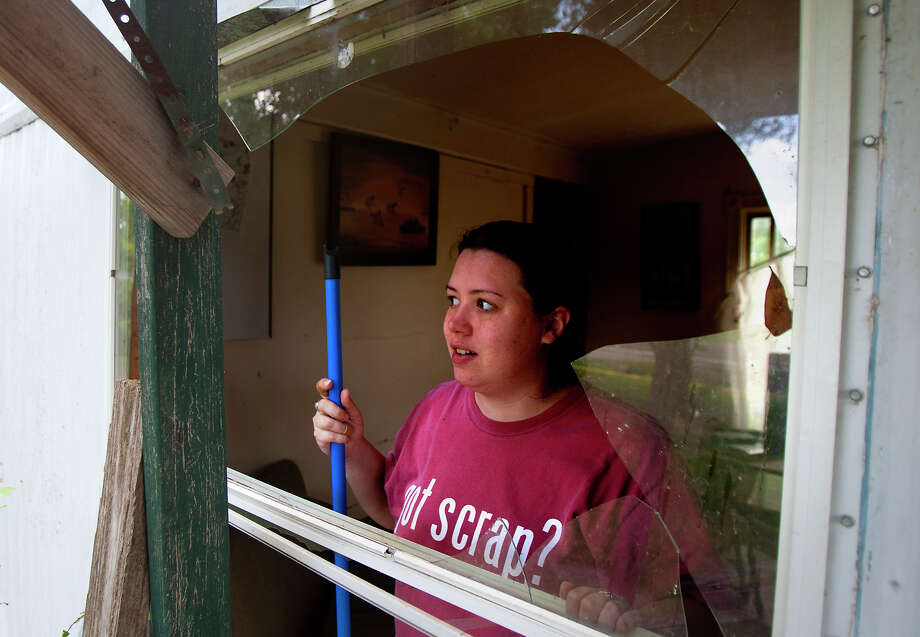 "Wendy Nickerson looks through a shattered window at her mother's home, Tuesday, June 11, 2013, in Dobbin. Two people were transported to the hospital after the home across the street exploded around 9 a.m. ""As soon as I got here, I hugged her,"" she said of her mom. Photo: Cody Duty, Houston Chronicle / © 2013 Houston Chronicle"