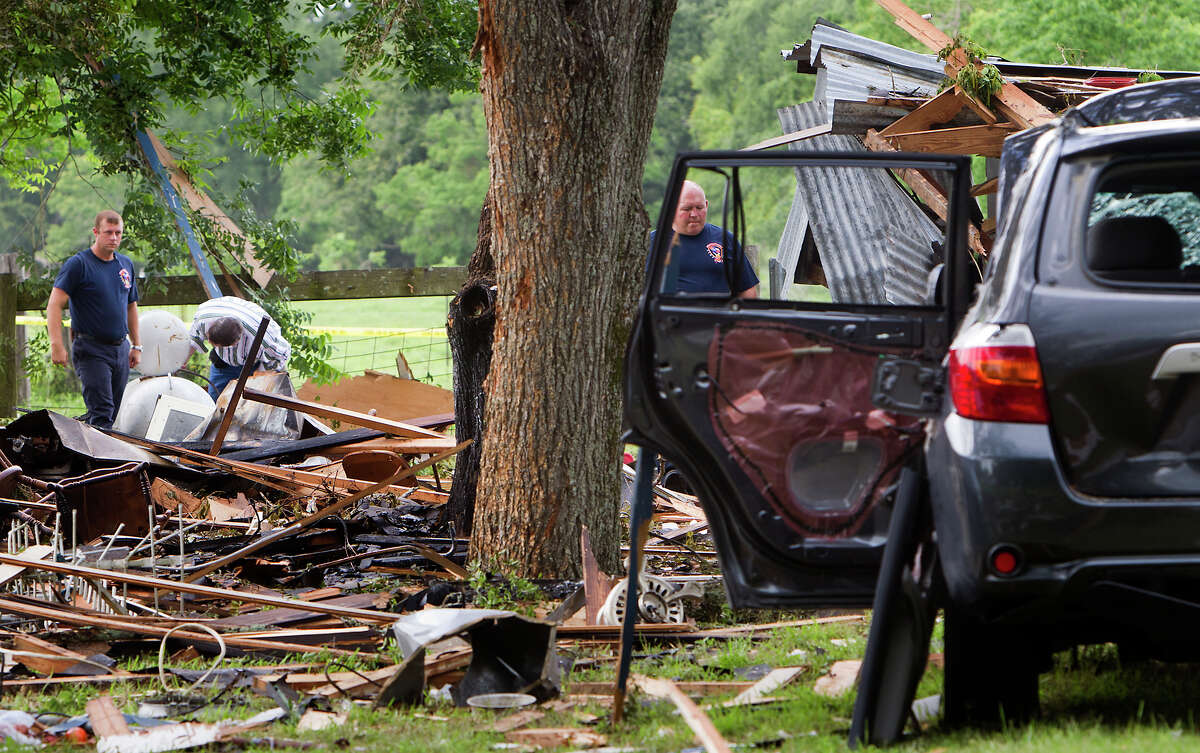 Investigators look through the debris after a home exploded, Tuesday, June 11, 2013, in Dobbin. Two people were transported to the hospital after the home exploded around 9 a.m.