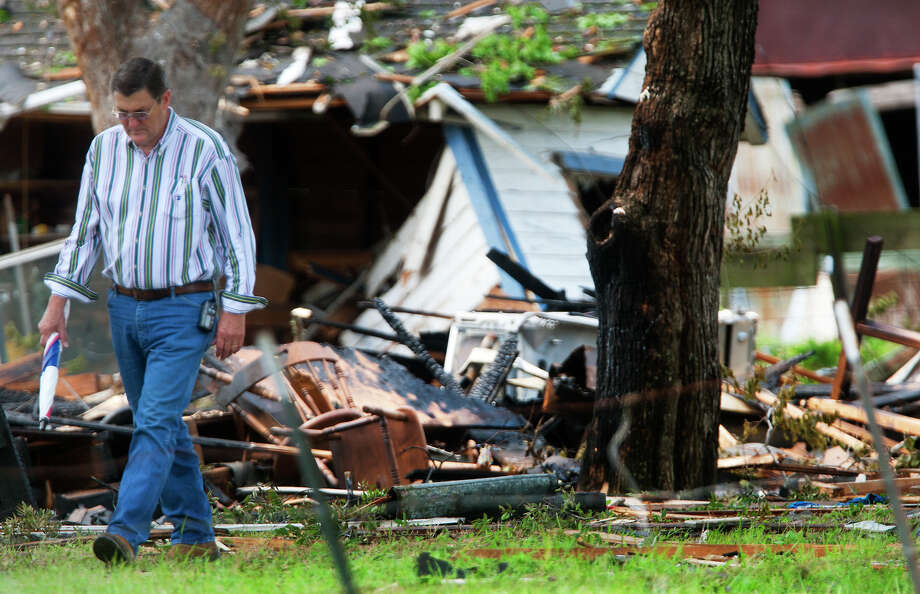 An investigator walks through the debris after a home exploded, Tuesday, June 11, 2013, in Dobbin. Two people were transported to the hospital after the home exploded around 9 a.m. Photo: Cody Duty, Houston Chronicle / © 2013 Houston Chronicle