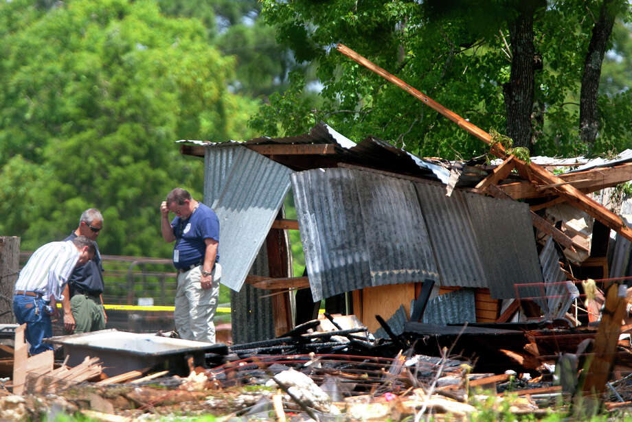Investigators look through the debris after a home exploded, Tuesday, June 11, 2013, in Dobbin. Two people were transported to the hospital after the home exploded around 9 a.m. Photo: Cody Duty, Houston Chronicle / © 2013 Houston Chronicle