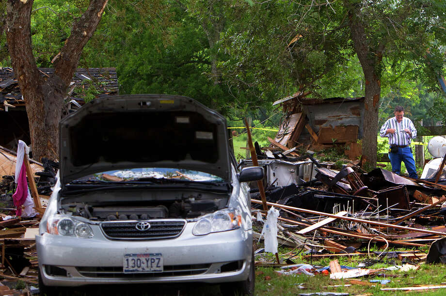 An investigator looks through the debris after a home exploded, Tuesday, June 11, 2013, in Dobbin. Two people were transported to the hospital after the home exploded around 9 a.m. Photo: Cody Duty, Houston Chronicle / © 2013 Houston Chronicle