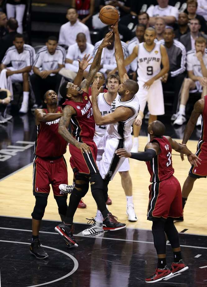Tim Duncan 21 of the Spurs shoots over Udonis Haslem 40 and Chris Bosh 1 of the Heat in the first quarter during Game 3 of the 2013 NBA Finals at the AT&T Center.