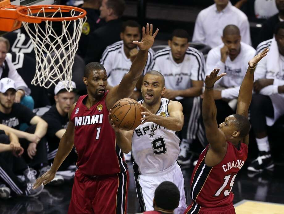Tony Parker 9 of the Spurs goes up for a shot against Chris Bosh 1 and Mario Chalmers 15 of the Heat in the first quarter during Game 3 of the 2013 NBA Finals.