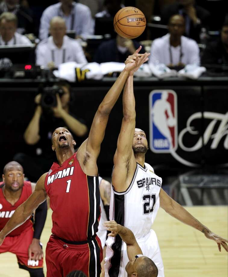 The Heat's Chris Bosh and Spurs' Tim Duncan compete for the ball at tip off  of Game 3 in their NBA Finals basketball series, Tuesday, June 11, 2013, in San Antonio.