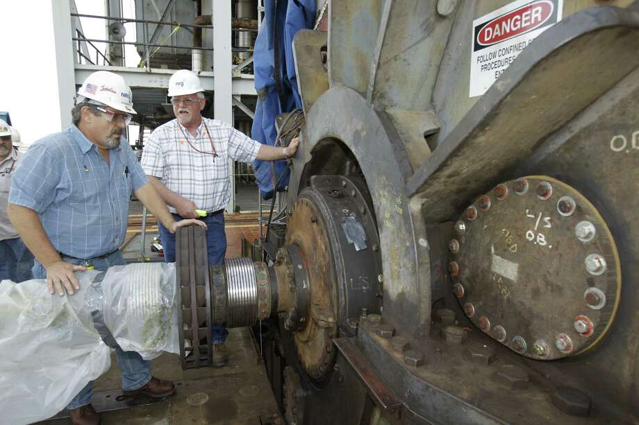 Ed Kascak, turbine maintenance crew leader (left), and Richard Brown, outage manager (right), talk about a generator shaft at NGR Energy's S.R. Bertron Power Plant, 2102 Miller Cut Off Road in La Porte. Photo: Melissa Phillip / Houston Chronicle