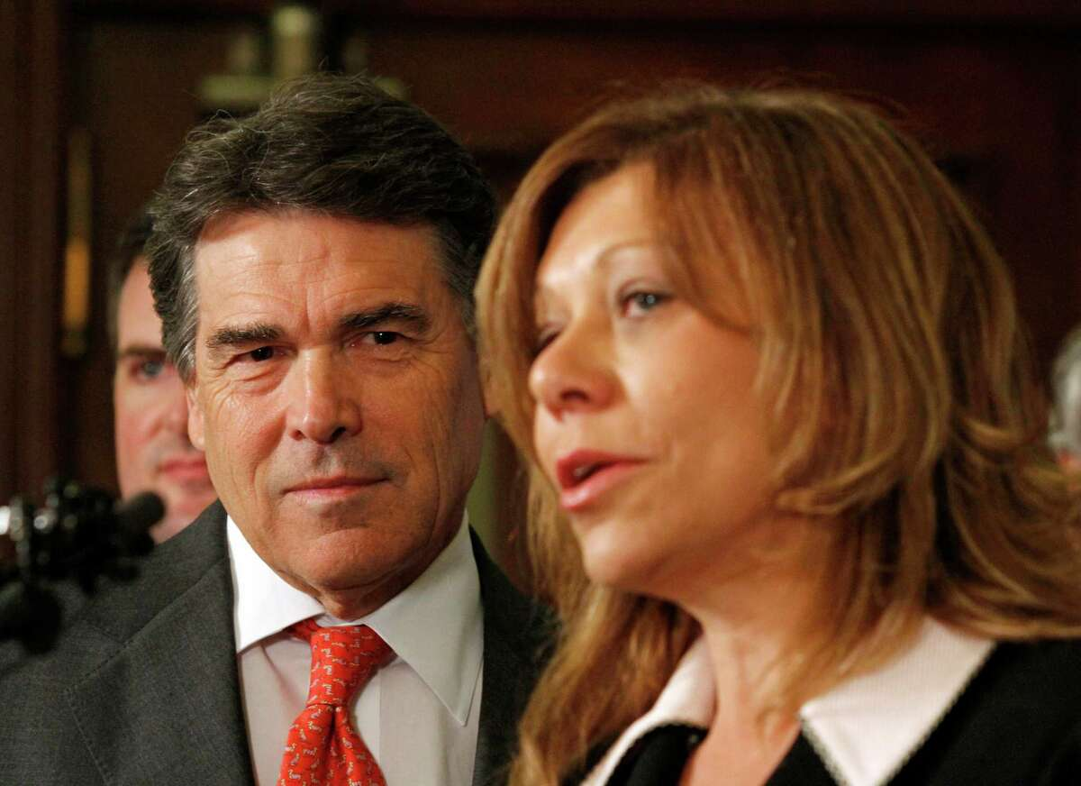Texas Gov. Rick Perry, left, listens to Sen. Joan Huffman, R-Southside Place, speak at a tort reform bill signing ceremony at the Capitol in Austin, Texas on Monday, May 30, 2011. The governor suggested that he would call a special session beginning Tuesday if the Senate can not revive and pass a key budget bill by the end of the day.(AP Photo/Jack Plunkett)
