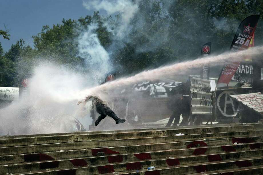 A protester is knocked back by a police water cannon as riot police advance toward Gezi Park from Taksim Square. Photo: Ed Ou / New York Times