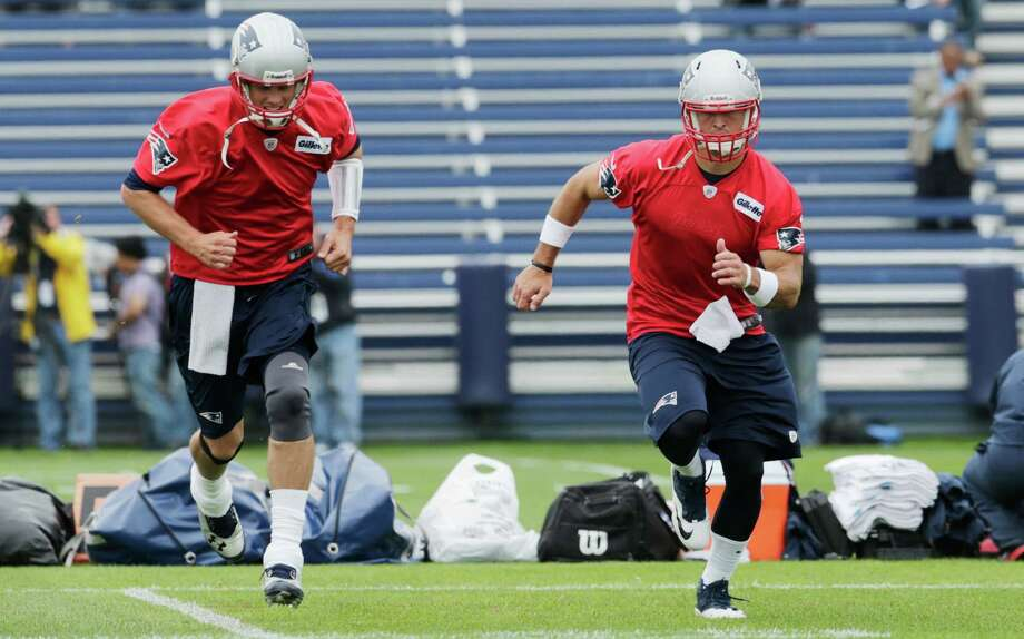 Newly signed Patriots quarterback Tim Tebow, right, sprints ahead of Tom Brady during New England's practice on Tuesday. Photo: Charles Krupa, STF / AP