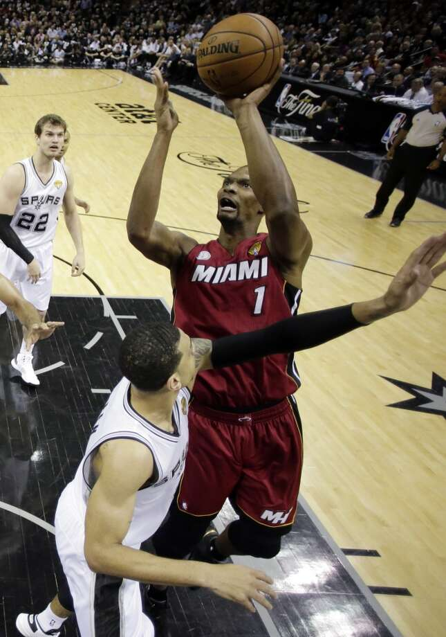 Chris Bosh (1) goes up for a shot against Danny Green. Photo: Eric Gay, Associated Press