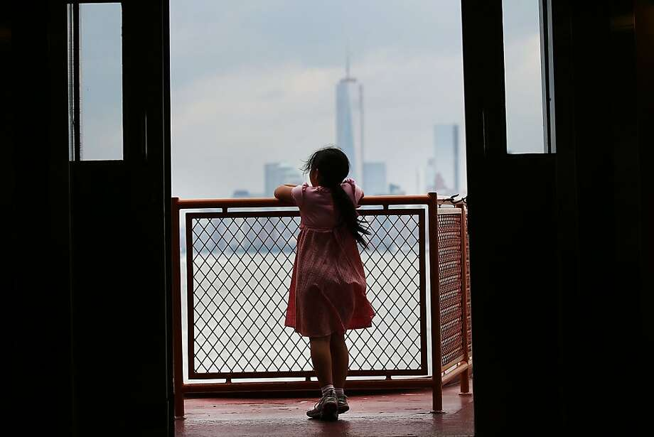 "NEW YORK, NY - JUNE 11: A young girl looks out at the island of Manhattan from the Staten Island Ferry on June 11, 2013 in New York City. In a highly anticipated speech, New York Mayor Michael Bloomberg has outlined a nearly $20 billion plan on Tuesday to help guard New York City from any future flood disasters. The proposal, which was given at the Brooklyn Navy Yard's Sandy-damaged Duggal Greenhouse, calls for sand dunes, levees, flood walls, bulkheads, and a proposed ""Seaport City."" (Photo by Spencer Platt/Getty Images) Photo: Spencer Platt, Getty Images"