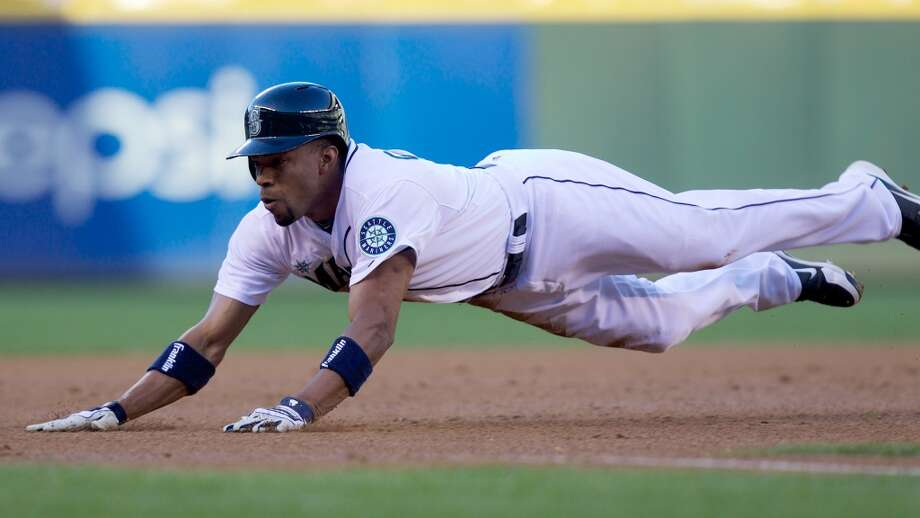 Endy Chavez #9 slides safely into third base after hitting a double and advancing on an error during the first inning. Photo: Stephen Brashear, Getty Images