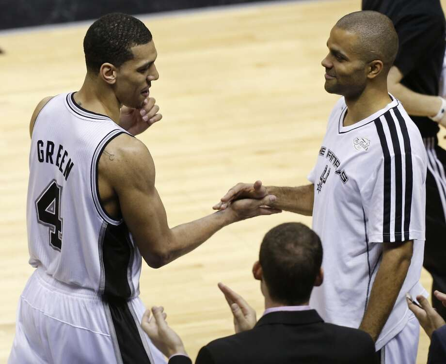 San Antonio Spurs' Danny Green shakes hands with San Antonio Spurs' Tony Parker on the bench during the second half of Game 3 of the 2013 NBA Finals against the Miami Heat Tuesday June 11, 2013 at the AT&T Center. The Spurs won 113-77.