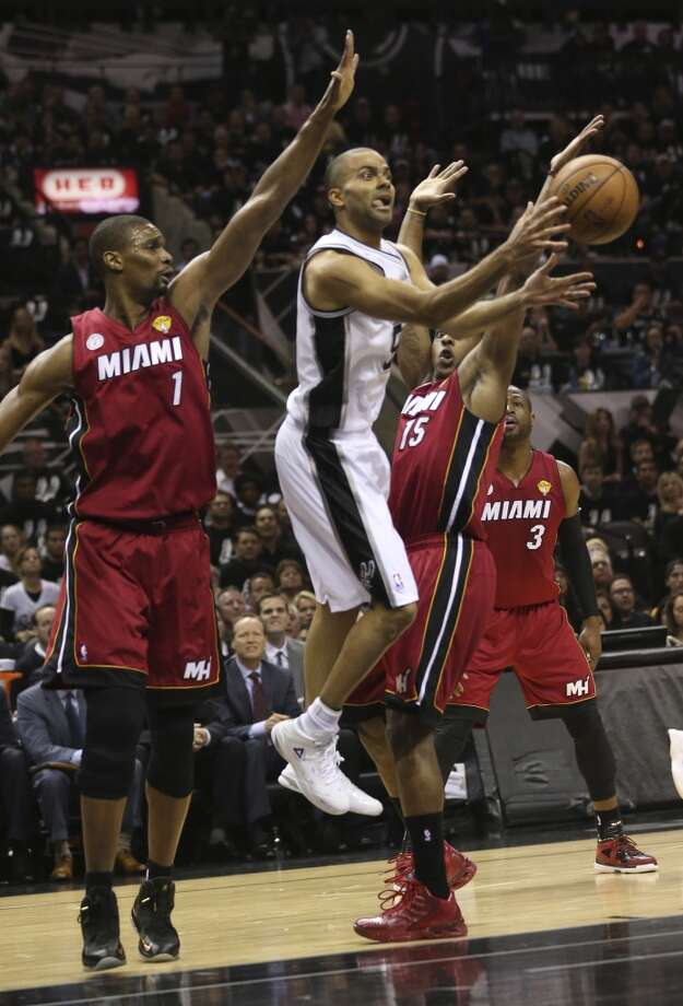San Antonio Spurs' Tony Parker drives between Miami Heat's Chris Bosh and Miami Heat's Mario Chalmers during the first half of Game 3 of the NBA Finals at the AT&T Center on Tue., June 11, 2013.