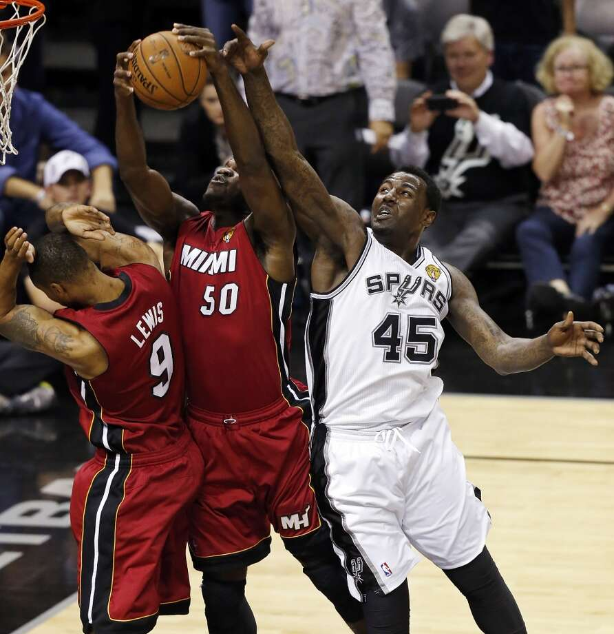 San Antonio Spurs' DeJuan Blair grabs for a rebound against Miami Heat's Rashard Lewis and Miami Heat's Joel Anthony during the second half of Game 3 of the 2013 NBA Finals Tuesday June 11, 2013 at the AT&T Center. The Spurs won 113-77.