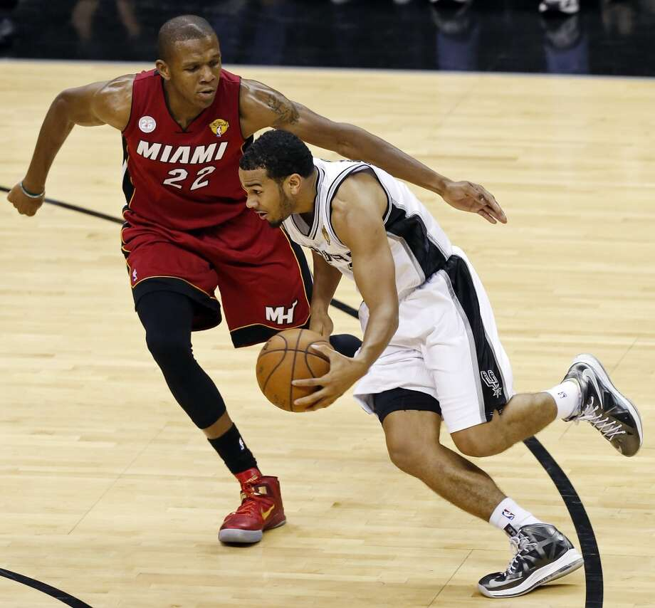 San Antonio Spurs' Cory Joseph looks for room  around Miami Heat's James Jones during the second half of Game 3 of the 2013 NBA Finals Tuesday June 11, 2013 at the AT&T Center. The Spurs won 113-77.