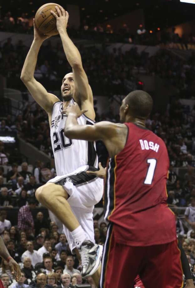 San Antonio Spurs' Manu Ginobili goes past Miami Heat's Chris Bosh on his way to the hoop during the first half of Game 3 of the NBA Finals at the AT&T Center on Tue., June 11, 2013.