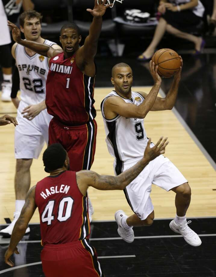 San Antonio Spurs' Tony Parker looks to pass between Miami Heat's Udonis Haslem and Miami Heat's Chris Bosh during the first half of Game 3 of the 2013 NBA Finals Tuesday June 11, 2013 at the AT&T Center.