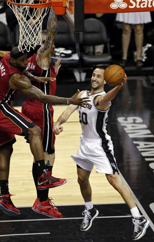 San Antonio Spurs' Manu Ginobili passes around Miami Heat's LeBron James and Miami Heat's Chris Andersen during the first half of Game 3 of the 2013 NBA Finals Tuesday June 11, 2013 at the AT&T Center.