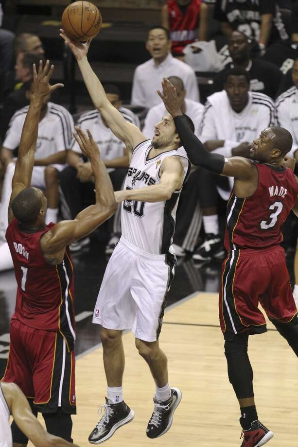 Spurs' Manu Ginobili (20) shoots between Heat's Chris Bosh and Heat's Dwyane Wade during the first half of Game 3 of the NBA Finals at the AT&T Center on Tuesday, June 11, 2013.