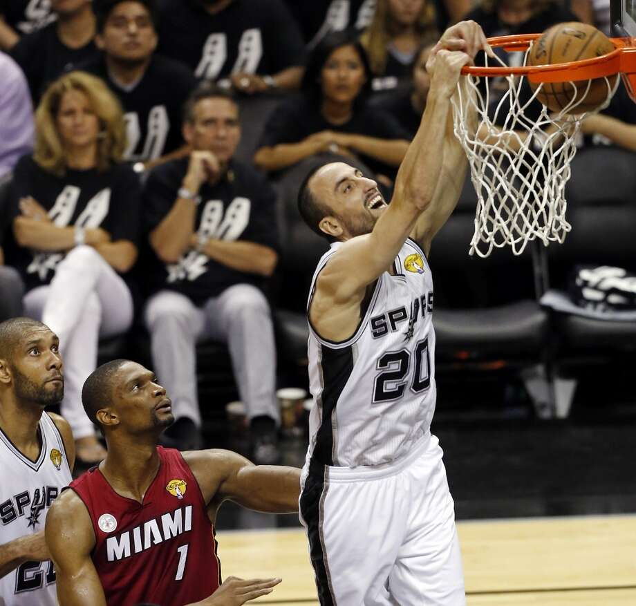 San Antonio Spurs' Manu Ginobili dunks around Miami Heat's Chris Bosh as San Antonio Spurs' Tim Duncan looks on during the first half of Game 3 of the 2013 NBA Finals Tuesday June 11, 2013 at the AT&T Center.