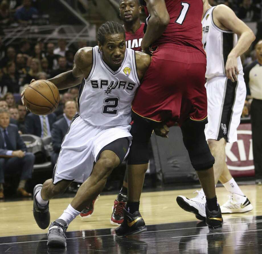 The Spurs' Kawhi Leonard drives around Miami's Chris Bosh. Leonard had another solid outing with 14 points and 12 rebounds. Photo: Jerry Lara / Express-News