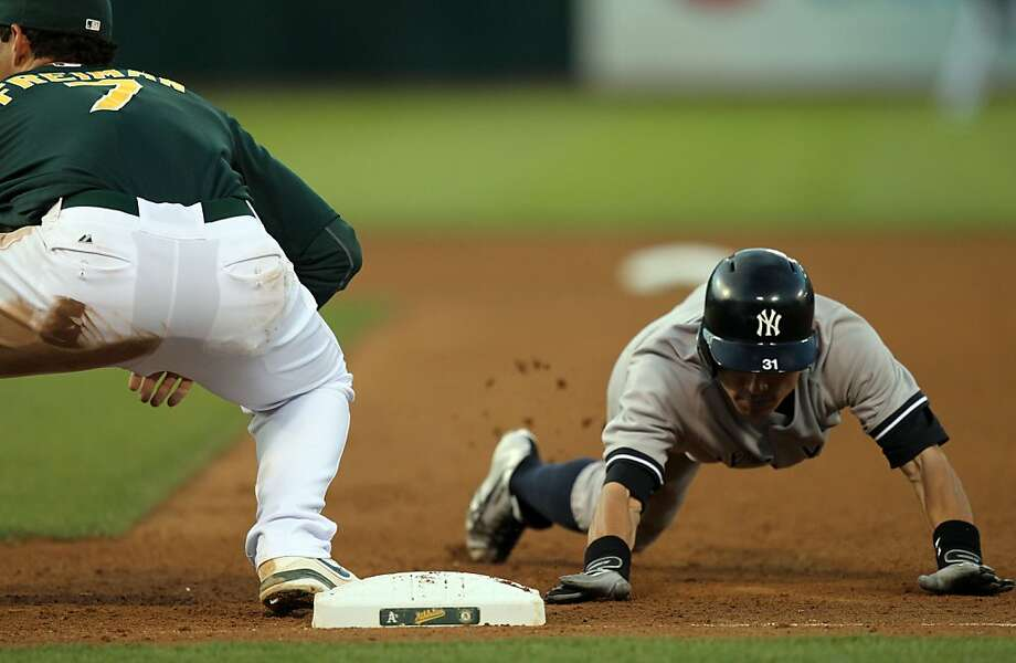 New York Yankees Ichiro Suzuki dives back into first base on a pick-off attempt by the Oakland Athletics Tuesday, June 11, 2013, in Oakland, Calif. Photo: Lance Iversen, The Chronicle