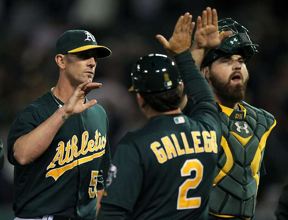 Oakland Athletics' pitcher Grant Belfour and catcher Derek Norris celebrate their 6-4 win over the New York Yankees with third base coach Mike Gallego Tuesday, June 11, 2013, in Oakland, Calif. Photo: Lance Iversen, The Chronicle